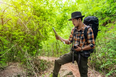 man traveler with backpack and map searching directions in the natural forest
