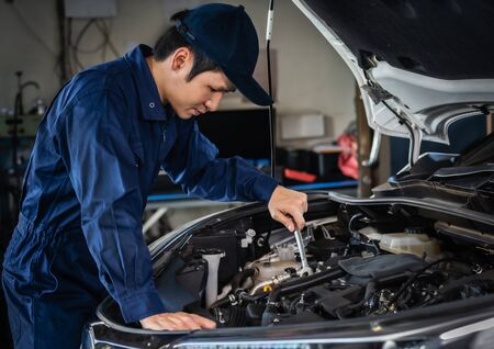 male mechanic using wrench to repair the engine, car service