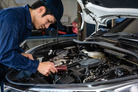 male mechanic using Tachometer checking engine of a car