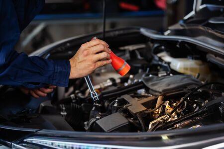 männlicher Mechaniker, der eine Taschenlampe hält und leuchtet, um ein Automotorproblem zu überprüfen Standard-Bild