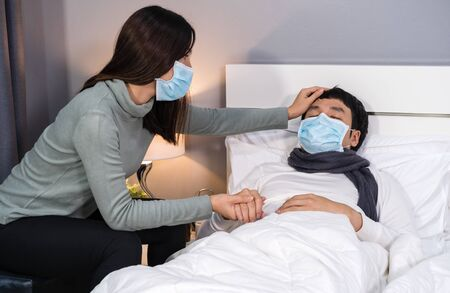 worried wife take care her sick husband while he sleeping on a bed at home, people must  be wearing medical mask protecting from coronavirus(covid-19) pandemic
