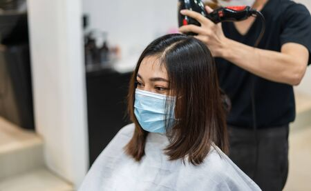hairdresser using hair dryer and comb to the hair of woman, people must be wering a medical mask to protection coronavirus (covid-19) pandemic. new normal concepts