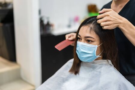 hairdresser cutting the hair to a female client, people must be wering medical mask to protection coronavirus (covid-19) pandemic. new normal concepts