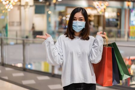 young woman wearing medical mask while shopping with bag at mall for prevention from coronavirus (Covid-19) pandemic. new normal concepts