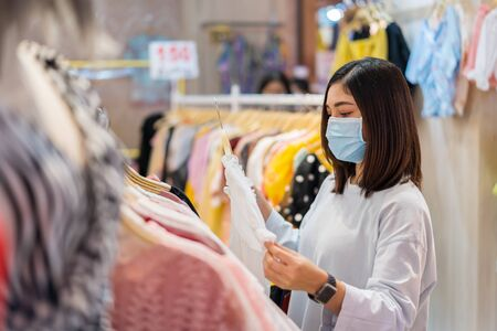young woman choosing clothes at shopping mall and her wearing medical mask for prevention from coronavirus (Covid-19) pandemic. new normal concepts