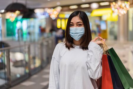 young woman shopping with bag at mall and her wearing medical mask for prevention from coronavirus (Covid-19) pandemic. new normal concepts