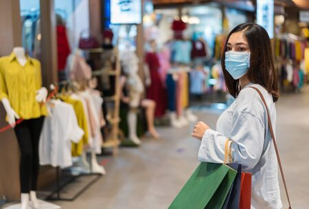 young woman holding shopping bag and looking to clothes at mall and her wearing medical mask for prevention from coronavirus (Covid-19) pandemic. new normal concepts