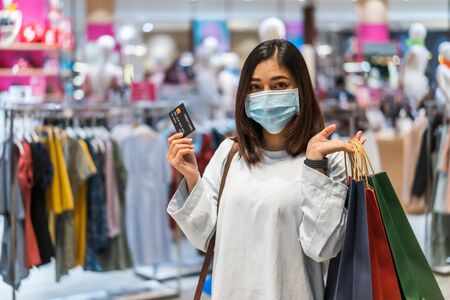 young woman wearing medical mask and holding credit card at shopping mall for prevention from coronavirus (Covid-19) pandemic. new normal concepts 免版税图像
