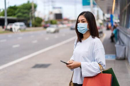 young woman holding smartphone and shopping bag waiting for bus at bus stop in city street and wearing face mask protective for spreading of coronavirus(covid-19) pandemic, new normal concept