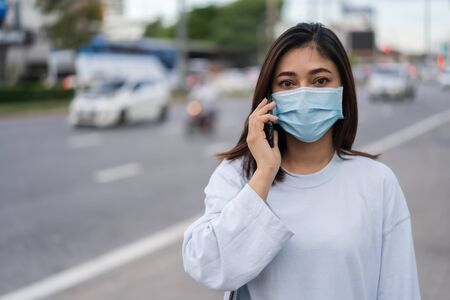 young woman talking with mobile phone in city street and wearing face mask protective for spreading of coronavirus(covid-19) pandemic, new normal concept
