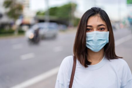 young woman in city street wearing face mask protective for spreading of coronavirus(covid-19) pandemic, new normal concept