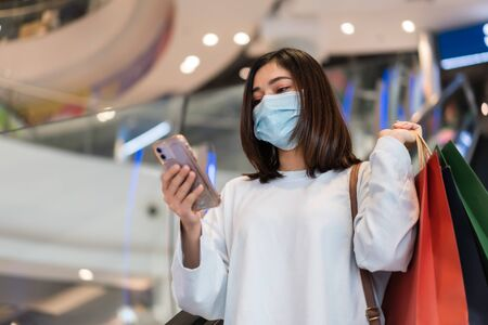 young woman using smartphone at shopping mall and her wearing medical mask for prevention from coronavirus (Covid-19) pandemic. new normal concepts