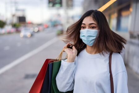 young woman holding shopping bag in city street and wearing face mask protective for spreading of coronavirus(covid-19) pandemic, new normal concept 免版税图像