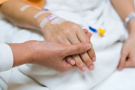 hand hold a patients hand on a bed in hospital