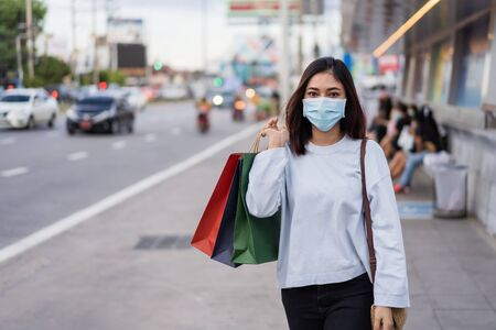 young woman holding shopping bag at bus stop in city street and wearing face mask protective for spreading of coronavirus(covid-19) pandemic, new normal concept