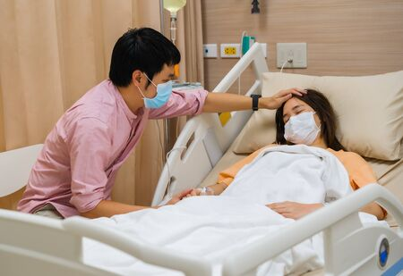 man visiting and take care female patient on a bed at hospital. people must be wearing medical mask to prevention coronavirus(covid-19) pandemic. Banque d'images