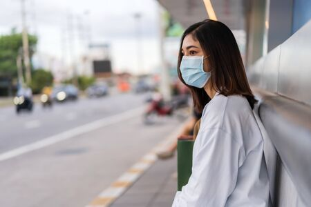 young woman waiting for bus at bus stop in city street and wearing face mask protective for spreading of coronavirus(covid-19) pandemic, new normal concept