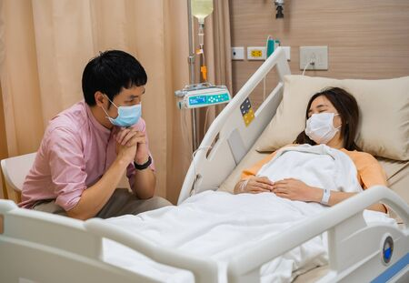 man visiting and take care female patient on a bed at hospital. people must be wearing medical mask to prevention coronavirus(covid-19) pandemic.