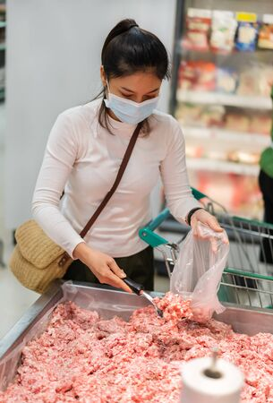 young asian woman buying  minced meat(pork) in food supermarket and her wearing medical mask for prevention coronavirus(covid-19) pandemic. new normal concept