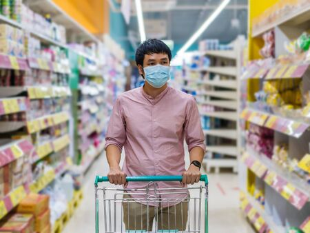 young asian man with shopping cart in supermarket department store and her wearing medical mask for prevention coronavirus(covid-19) pandemic. new normal concept