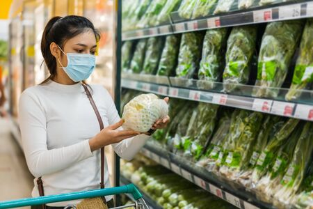 young asian woman choosing vegetables while shopping food in supermarket and her wearing medical mask for prevention coronavirus(covid-19) pandemic. new normal concept 免版税图像