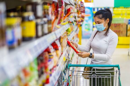 young asian woman with shopping cart in supermarket department store and her wearing medical mask for prevention coronavirus(covid-19) pandemic. new normal concept 免版税图像