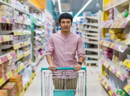 young asian man with shopping cart in supermarket department store