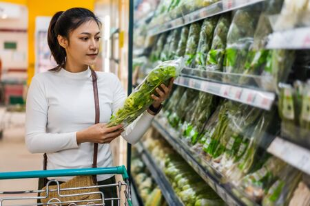 young asian woman choosing vegetables while shopping food in supermarket
