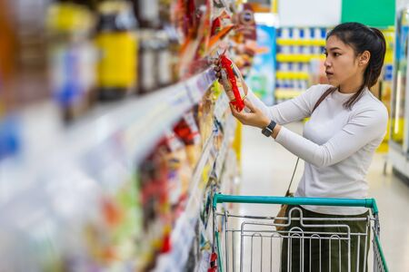 young asian woman with shopping cart in supermarket department store  免版税图像