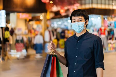 young asian man shopping with bag at mall and his wearing medical mask for prevention from coronavirus (Covid-19) pandemic. new normal concepts 免版税图像
