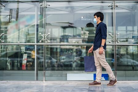 young asian man walking and holding shopping bag in front of store and his wearing medical mask for prevention from coronavirus (Covid-19) pandemic. new normal concepts
