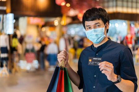 young asian man wearing medical mask and holding a credit card at shopping mall for prevention from coronavirus (Covid-19) pandemic. new normal concepts