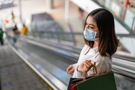 young asian woman shopping with bag at mall and her wearing medical mask for prevention from coronavirus (Covid-19) pandemic. new normal concepts 免版税图像