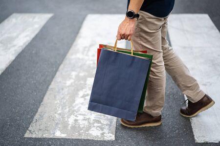 man holding shopping bag walking cross the street in city