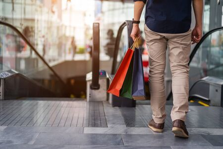 Close up of young man leg carrying shopping bags while walking in shopping mall