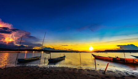 wooden boat at banks of the river with sunset and lightning in Khonburi, Nahon Ratchasima province, Thailand.