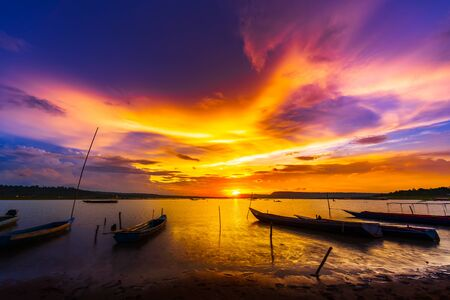 wooden boat at banks of the river with sunset in Khonburi, Nahon Ratchasima province, Thailand.