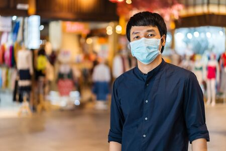 young asian man wearing medical mask at the shopping mall for prevention from coronavirus (Covid-19) pandemic. new normal concepts 免版税图像