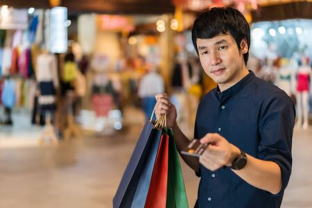 young asian man wearing medical mask and holding a credit card at shopping mall  免版税图像