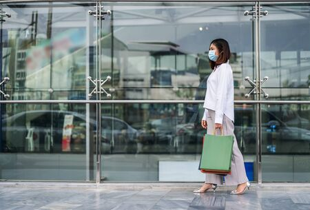 young asian woman walking and holding shopping bag in front of store and his wearing medical mask for prevention from coronavirus (Covid-19) pandemic. new normal concepts 免版税图像