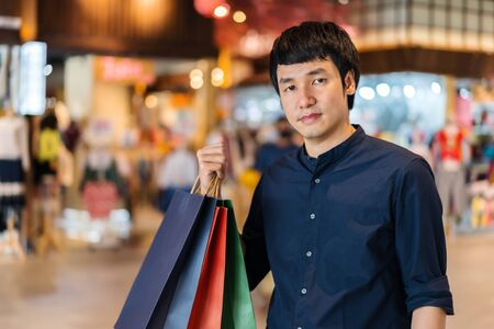 young asian man shopping with bag at mall 免版税图像