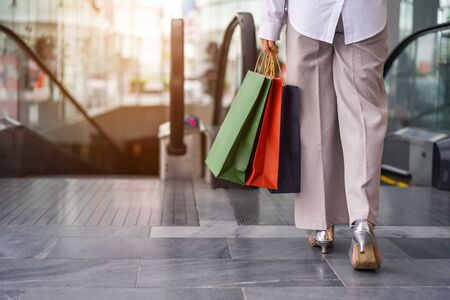 Close up of young woman leg carrying shopping bags while walking in shopping mall