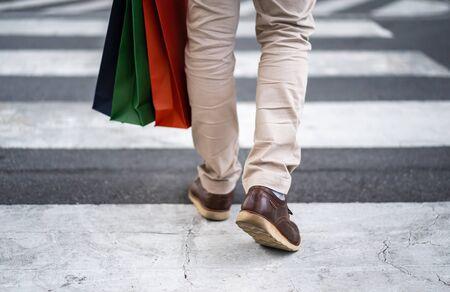 man holding shopping bag walking cross the street in city Stockfoto