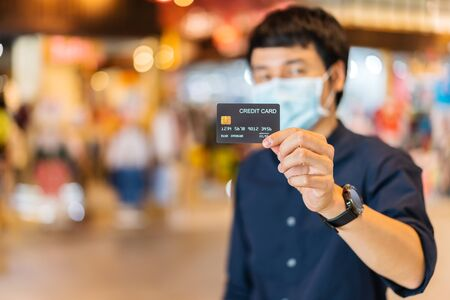 credit card with young asian man wearing medical mask at the shopping mall for prevention from coronavirus (Covid-19) pandemic. new normal concepts