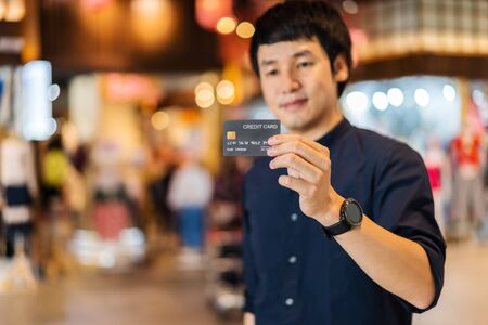 credit card with young asian man at the shopping mall