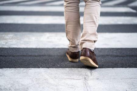 close up legs of man walking cross the street in city