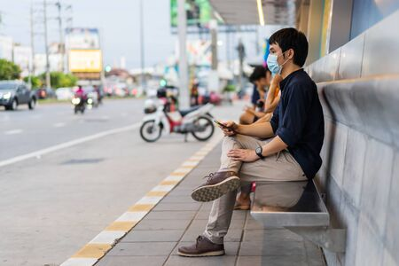 young asian man holding smartphone and waiting for bus at bus stop in city street and wearing face mask protective for spreading of coronavirus(covid-19) pandemic, new normal concept