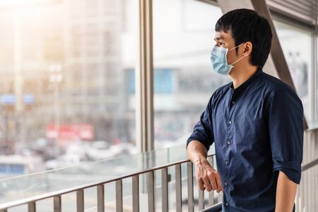 young asian man wearing medical mask for prevention from coronavirus (Covid-19) pandemic in the city. new normal concepts