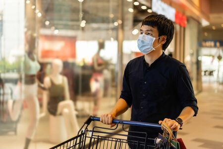 young asian man with shopping cart in department store and his wearing medical mask for prevention coronavirus(covid-19) pandemic. new normal concept