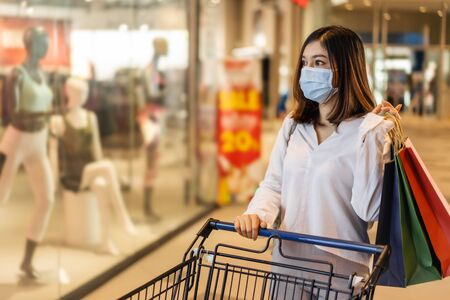 young asian woman with shopping cart in department store and her wearing medical mask for prevention coronavirus(covid-19) pandemic. new normal concept